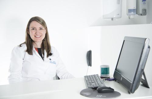 Foto de la doctora sentada en su escritorio sonriente